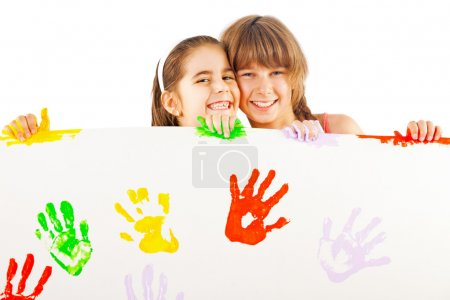 Photo for Two smiling little girls holding white sheet with colourful hand prints - Royalty Free Image