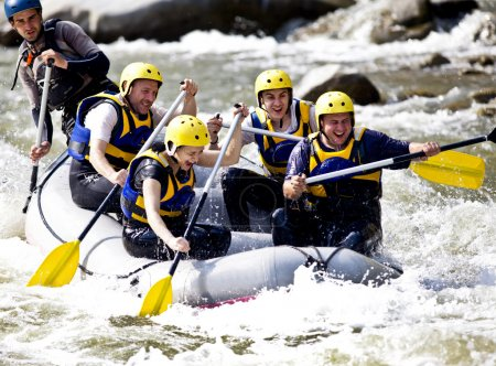 Photo for Group of happy with guide whitewater rafting and rowing on river - Royalty Free Image
