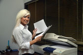 Pretty girl scans documents at the office
