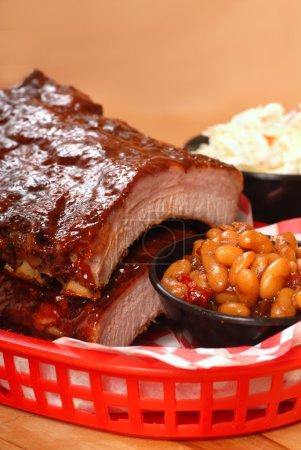 Photo pour Délicieuses côtes de barbecue avec haricots, salade de chou et sauce barbecue acidulée - image libre de droit