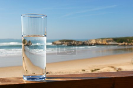 Glass of water with view on beach