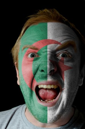Face of crazy angry man painted in colors of algeria flag