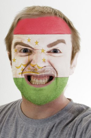 Face of crazy angry man painted in colors of Tajikistan flag