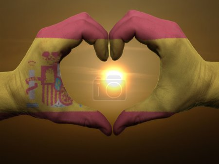Photo for Gesture made by spain flag colored hands showing symbol of heart and love during sunrise - Royalty Free Image
