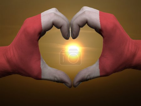 Heart and love gesture by hands colored in peru flag during beau
