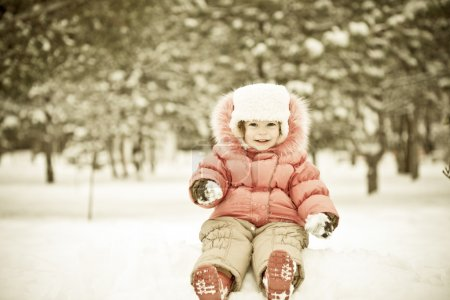 Photo for Child playing at snowballs in winter park - Royalty Free Image