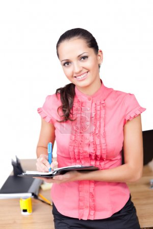 Young happy smiling business woman taking notes at the office