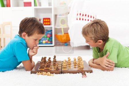 Foto de Niños jugando ajedrez tirado en el piso y pensar intensamente - Imagen libre de derechos