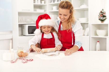 Photo pour Femme heureuse et jeune fille, qui s'étend de la pâte à biscuits Noël ensemble - image libre de droit