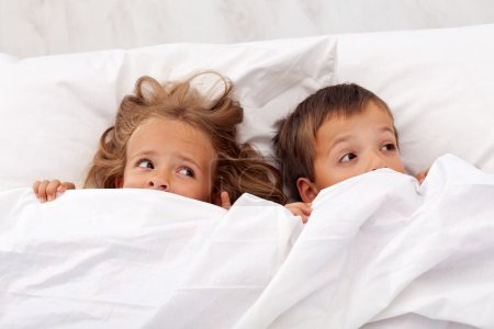 Photo for Kids afraid laying in bed and pulling the quilt on their heads - Royalty Free Image