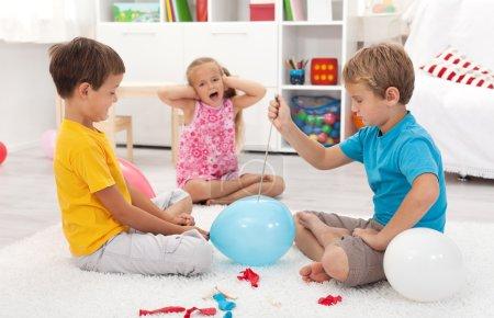 Kids popping balloons