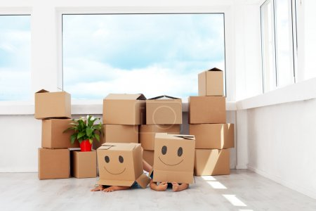 Photo for Kids having fun while moving in a new home playing with boxes - Royalty Free Image