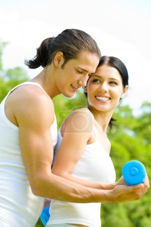 Young happy smiling couple in sport wear doing fitness exercise