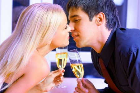 Young happy couple with champagne kissing at restaurant