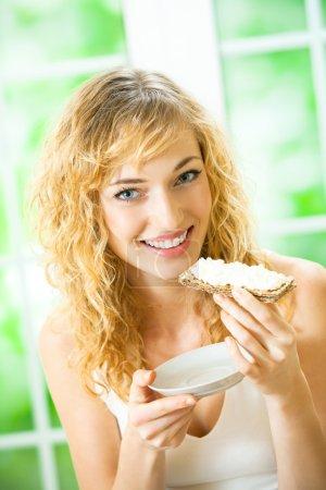 Photo pour Portrait de jeune femme heureuse mangeant du pain croustillant avec du fromage à la maison - image libre de droit