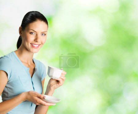 Young happy woman drinking coffee, outdoors