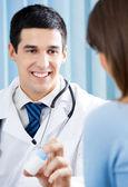 Usmívající se doktor s lék a pacient v kanceláři