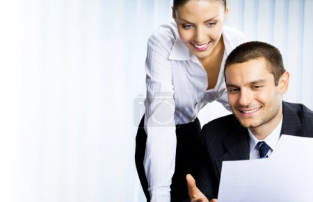 Photo for Two young happy smiling successful businesspeople working with document or contract at office - Royalty Free Image