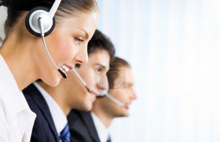 Foto de Tres feliz sonriente a joven cliente apoyan los operadores de telefonía en el lugar de trabajo - Imagen libre de derechos