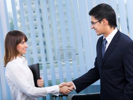 Two happy businesspeople, or businessman and client, handshaking