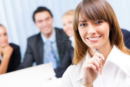 Businesswoman and colleagues on background, at office