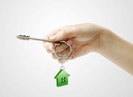main tenant les clés avec un porte-clés en forme de la maison.