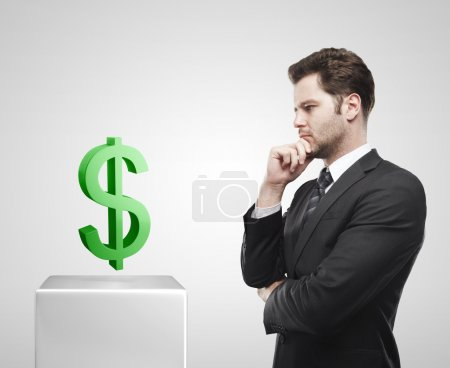 Young businessman look at the green US dollar sign on a white pedestal.