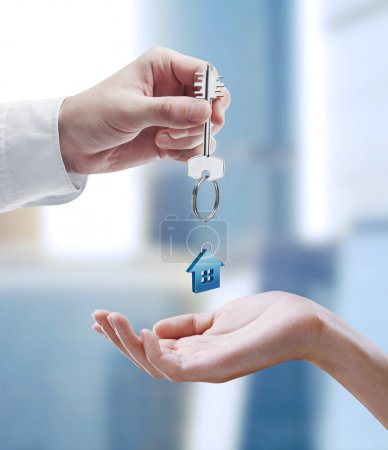 Photo for Man is handing a house key to a woman. Key with a keychain in the shape of the house - Royalty Free Image