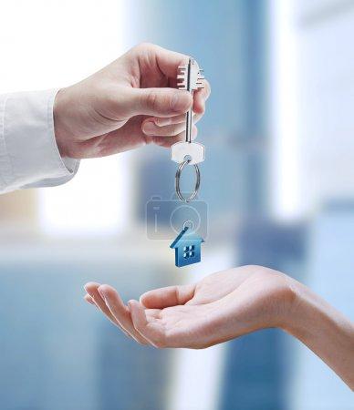 Photo pour L'homme donne la clé d'une maison à une femme. Clé avec un porte-clés en forme de maison - image libre de droit