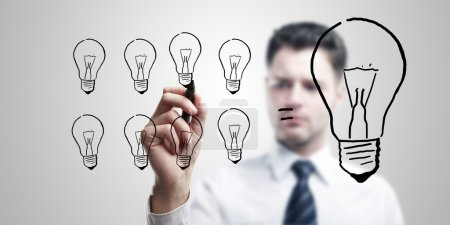 Photo pour Homme d'affaires jeune dessin de nombreuses petites ampoules égale un grand. homme venir avec une idée sur un écran de verre avec marqueur noir. sur un fond gris - image libre de droit