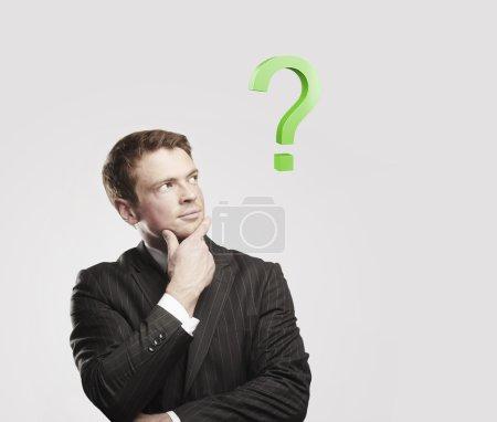 Portrait d'un jeune homme avec point d'interrogation vert au-dessus de sa tête