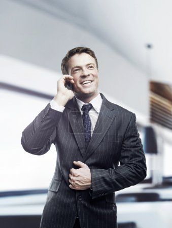 Portrait of happy businessman talking on mobile standing in office, smiling