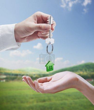 Photo pour L'homme est remise à une clé de la maison à une femme. clés avec un porte-clés en forme de la maison. sur fond de nature - image libre de droit