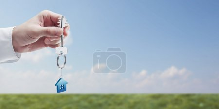 Hand holding key with a keychain in the shape of the house.