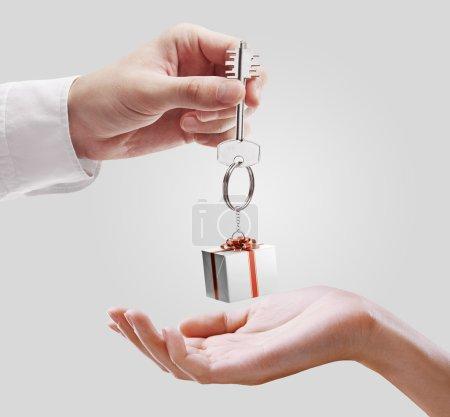 Photo pour L'homme est remise à une clé de la maison à une femme. clés avec un porte-clés en forme de la boîte-cadeau. clé de la maison sur un fond gris. - image libre de droit