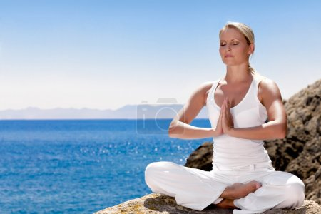 Photo for Beautiful positive girl clothing in white sit at the seaside on the rock and meditating in yoga pose - Royalty Free Image