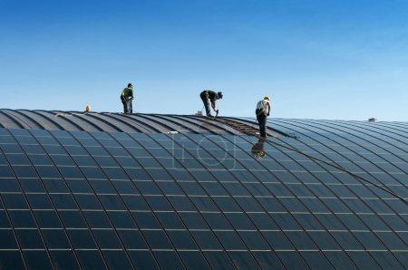 Foto de Installazione di pannelli solari sul tetto di edificio de las Naciones Unidas. Tre operai al lavoro. - Imagen libre de derechos