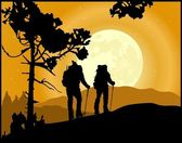 Two climbers in silhouette climbing the mountain on the moonlight