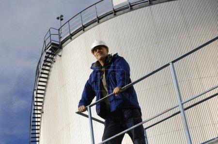 Photo pour Travailleur pétrolier et gazier avec une grande tour de stockage de combustible en arrière-plan - image libre de droit