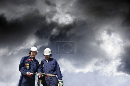 Photo for Industrial workers, engineers, under a dark cloudy industrial sky, finishing work concept - Royalty Free Image