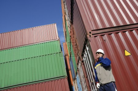 Photo for Worker in port with stacks of cargo shipping containers in background - Royalty Free Image