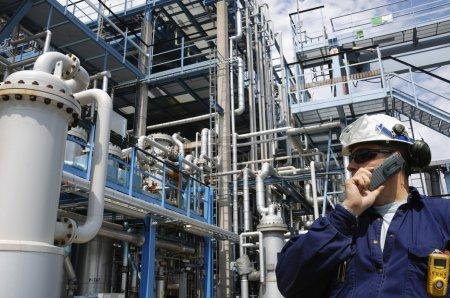 Photo pour Travailleur de raffinerie avec une grande industrie pétrochimique en arrière-plan - image libre de droit