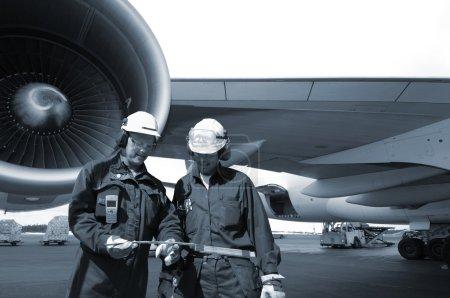 Photo pour Deux mécaniciens, ingénieurs en gros plan, grand avion de ligne en arrière-plan, concept de tonalité bleue - image libre de droit
