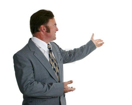 Photo pour Un homme d'affaires en costume gris faisant un geste vers un graphique. Isolé . - image libre de droit