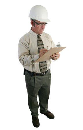 Photo pour Un inspecteur de sécurité de construction portant un dur lunettes de chapeau et de la sécurité et en examinant une liste - pleine vue isolée - image libre de droit