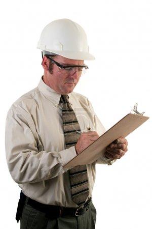 Photo pour Un inspecteur de sécurité de construction avec des lunettes et un chapeau dur inspecter un chantier - image libre de droit