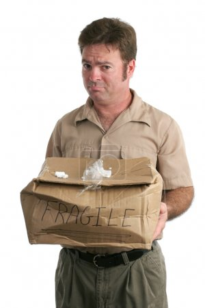 Photo for A delivery man holding out a smashed package and looking very sorry. Isolated. - Royalty Free Image