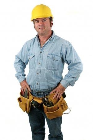 Photo pour Un ouvrier du bâtiment beau, fier, portant une ceinture d'outil et chapeau dure. - image libre de droit