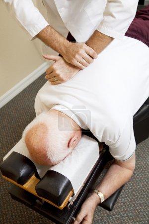 Foto de Primer plano de las manos de quiroprácticos ajuste de la espina dorsal de un hombre mayor. - Imagen libre de derechos
