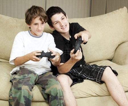 Photo for Two brothers at home playing video games together. - Royalty Free Image